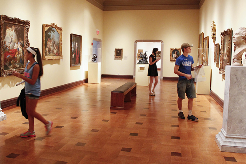 students browse an open art exhibit in a gallery at Ball State
