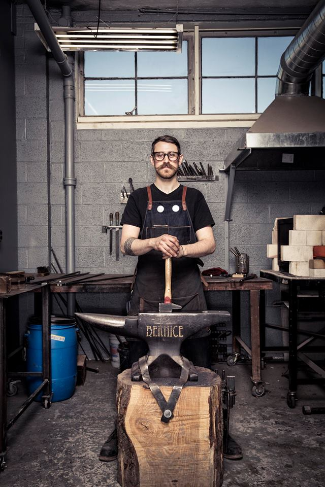Image of the artist Gabriel Craig posing with an anvil and hammer in his metals workshop.