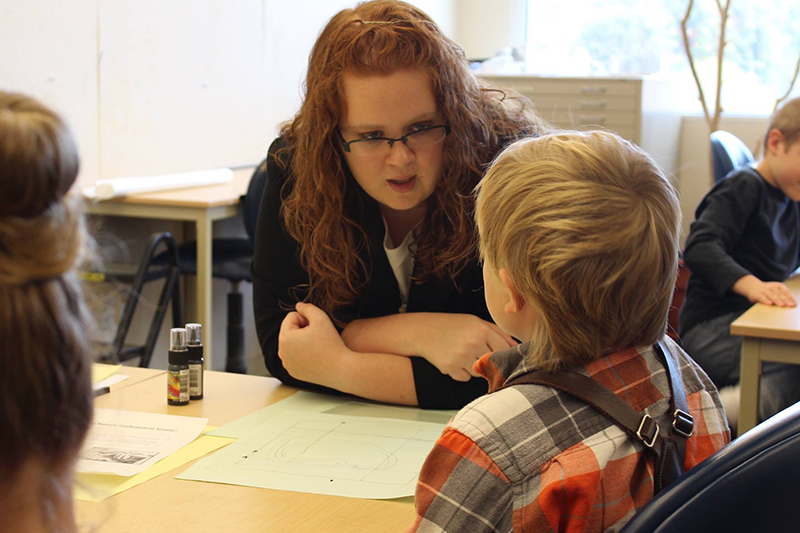 student teacher teaches child student about art
