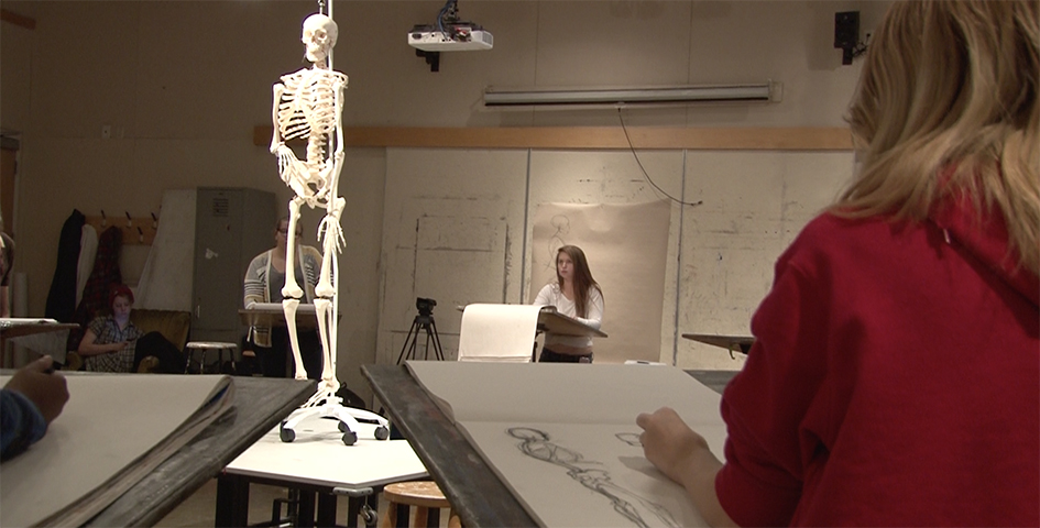 Students drawing a model skeleton