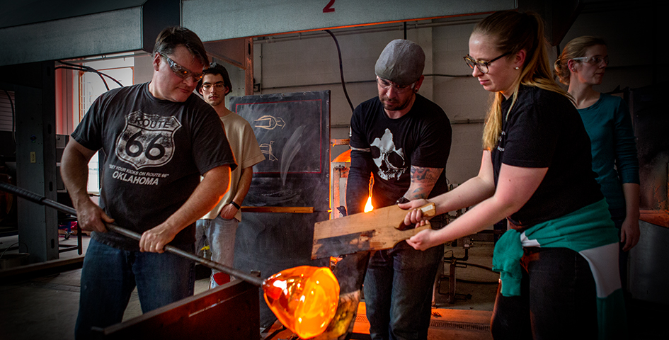 students and instructor blowing glass