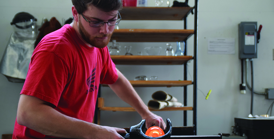 student blowing glass