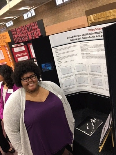 Photo of High School Student Presenting Poster at Conference