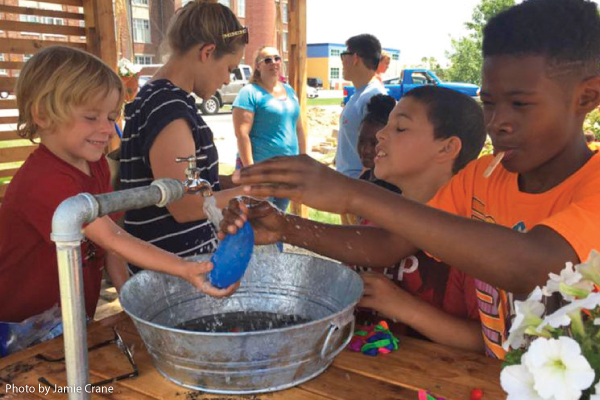 Rainwater is collected from the butterfly shaped roof, runs down a gutter and into an open bucket with a spigot to allow children to play with the collected water. (Photo courtesy of Jamie Crane.)