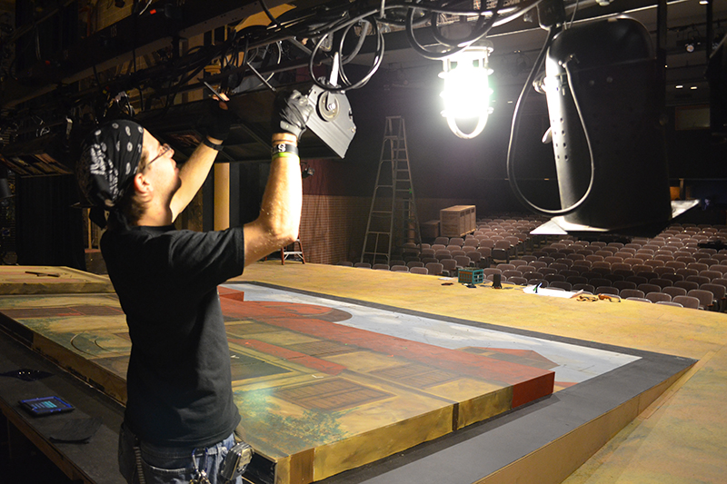 student fixing lighting in scene shop
