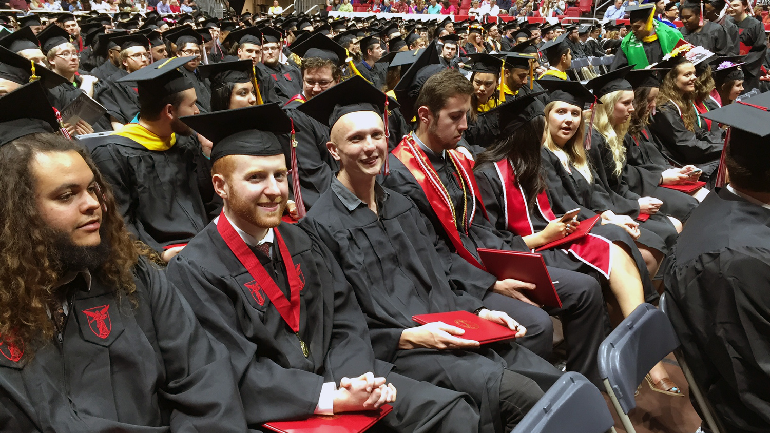 students at commencement ceremonies, wearing academic regalia