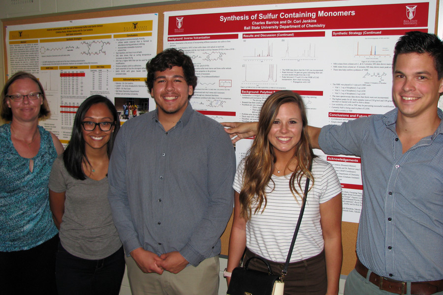 people posing in front of a research poster