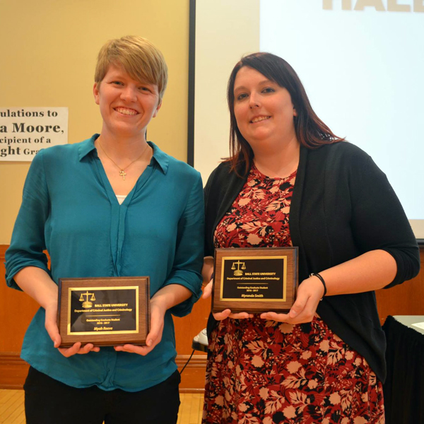 two students hold award plaques