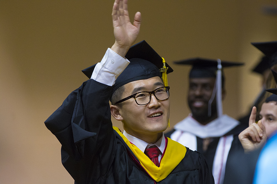 Graduating student waving