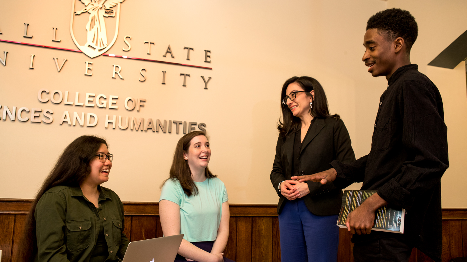 alum Janet Arias speaks with students outside the Dean's office