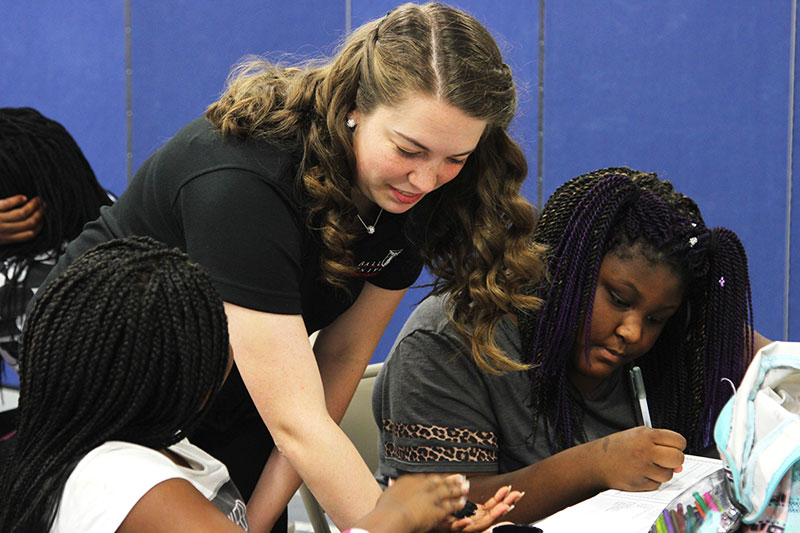 A teacher working with a group of students.