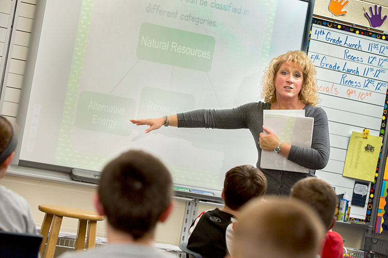 A teacher giving instruction in a classroom.
