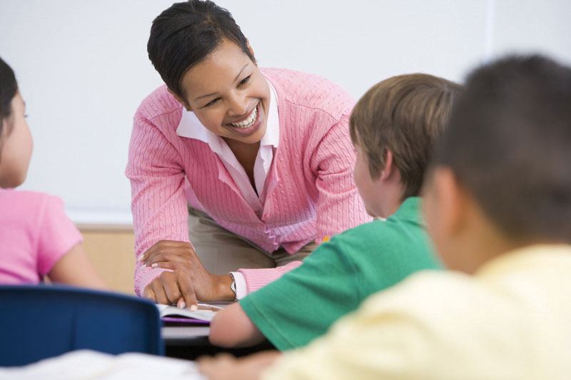 A teacher smiling as she works with a group of students.
