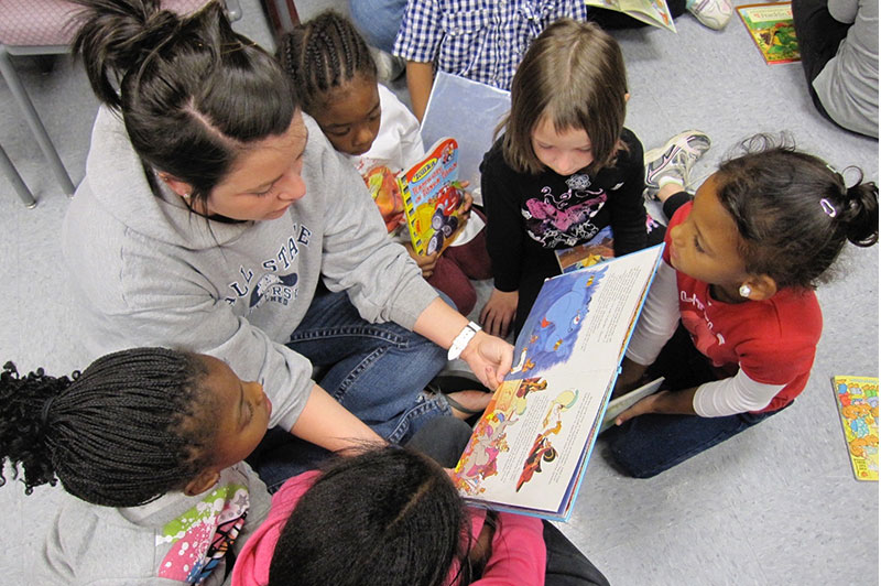A student reading a book to a group of children.