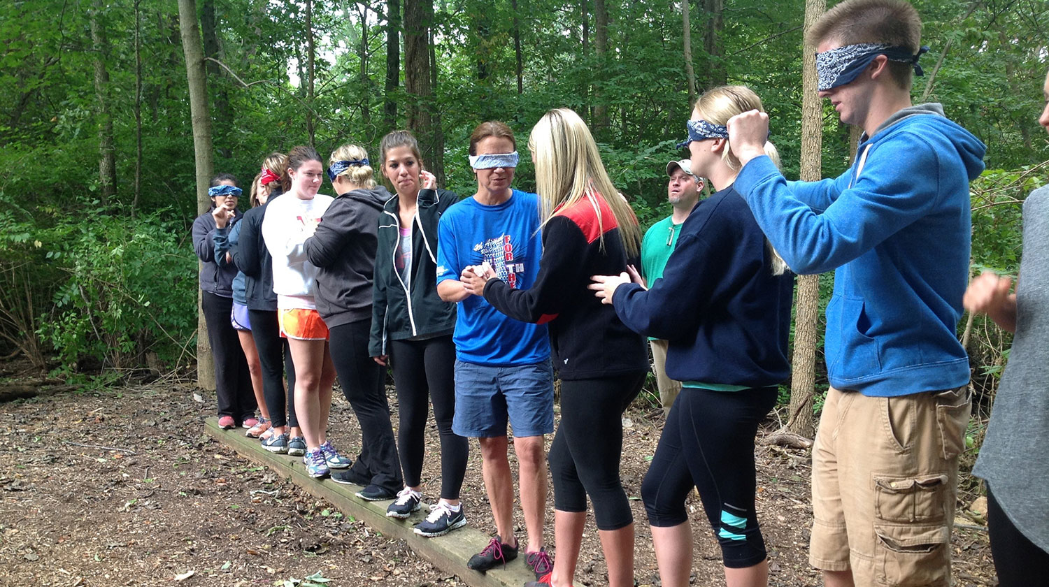 Students working together at an activity in the woods.