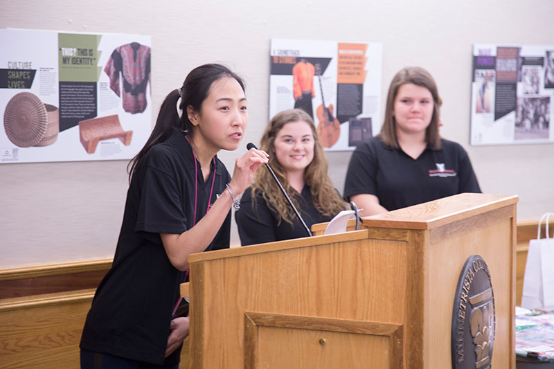 Graduate students standing at a podium giving a presentation.