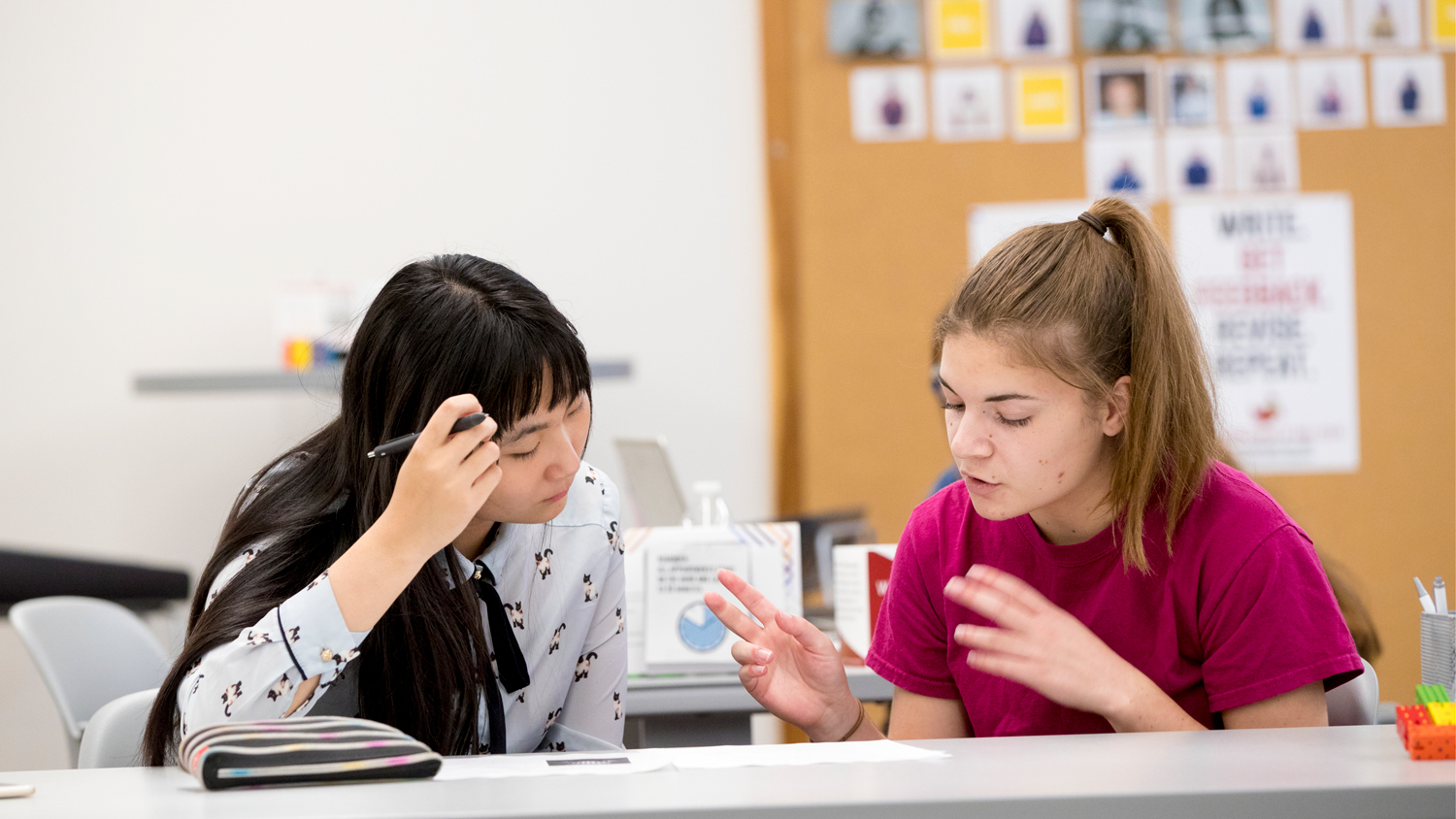 two female students talking while looking at a book