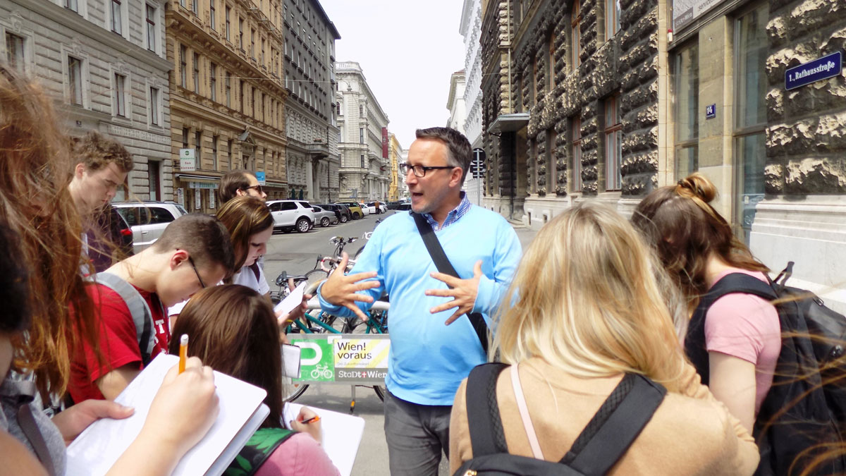 group leader speaking to students on a street in Vienna