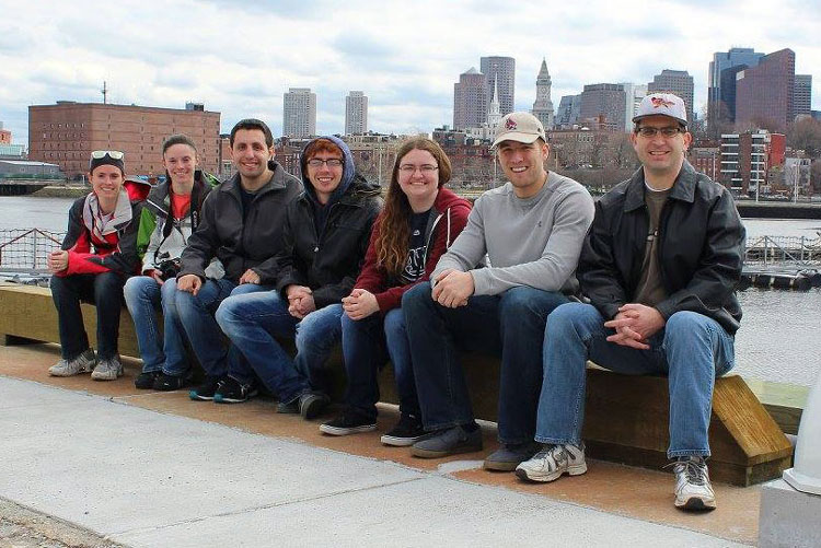 group of people posing for photo in front of a river and city skyline