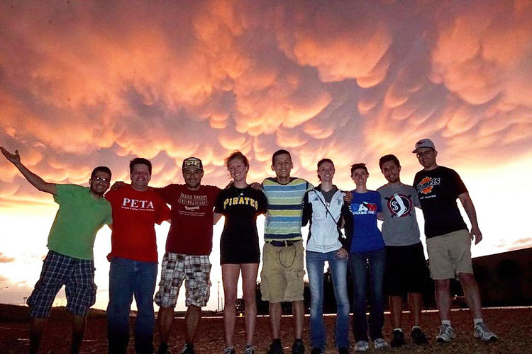 group of students posting in front of a vivid sky
