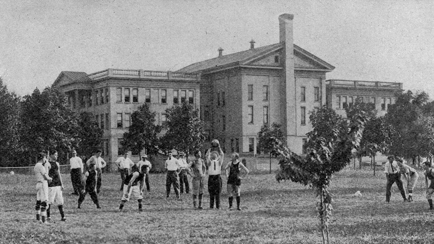 Men playing volleyball outside what is now the Administration Building.