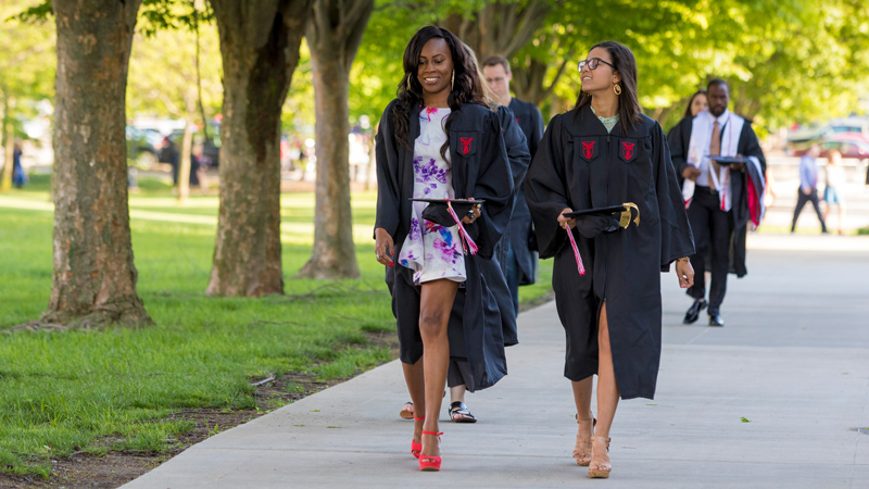 students walking in commencement gowns