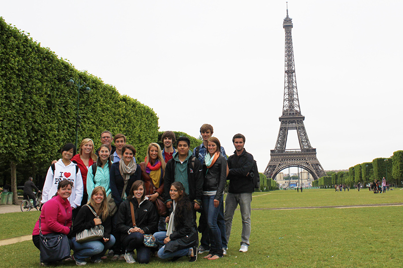 group of study abroad students pose for photo in front of Eiffel Tower