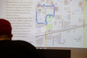 A map is displayed on a projector screen with a head in front of it