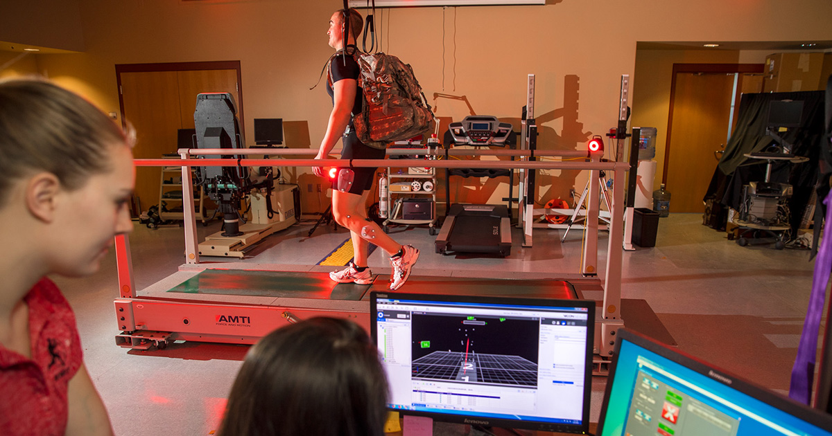 Two students look-on as a man runs on a treadmill.