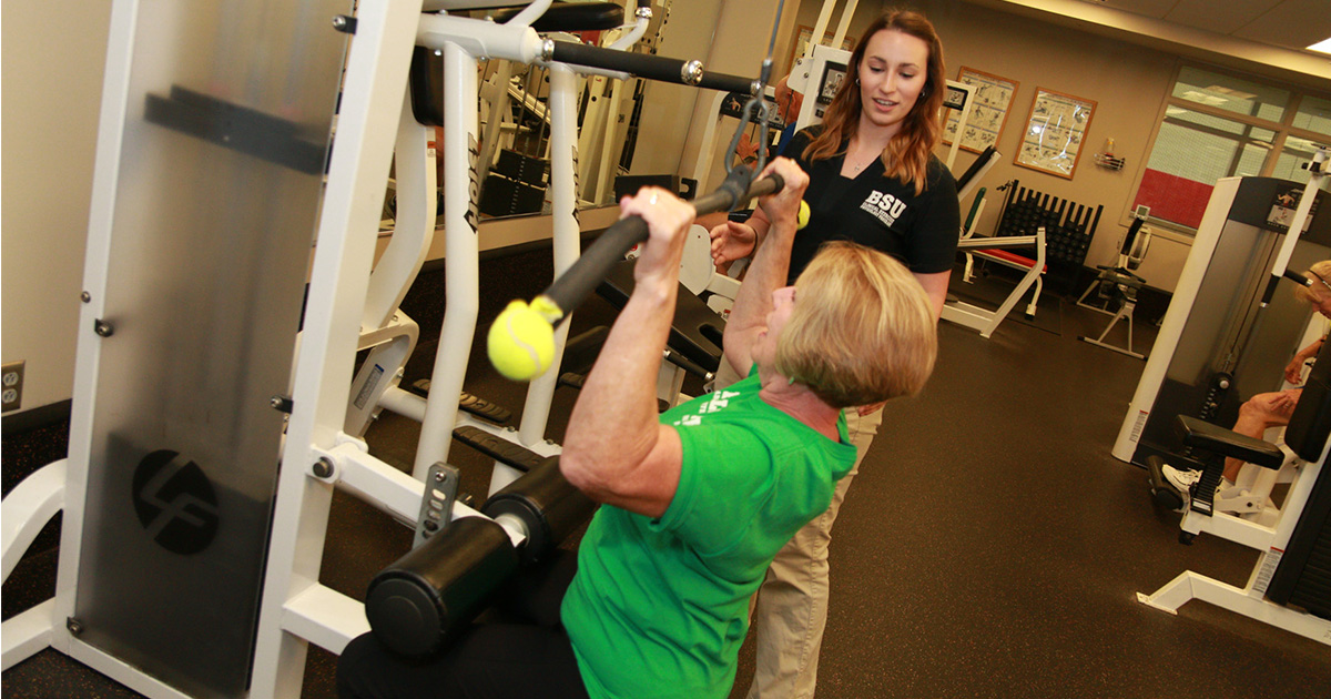 A woman lifts weights as a student looks on.