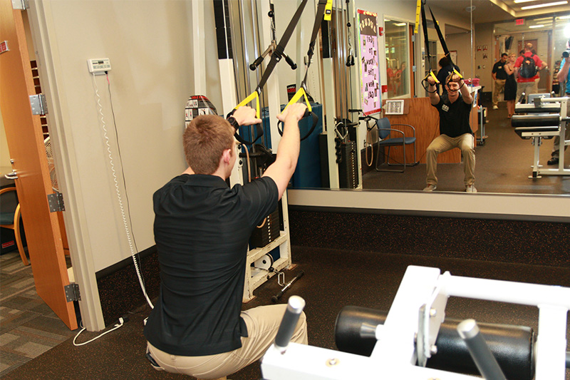 Student works on exercise machine.