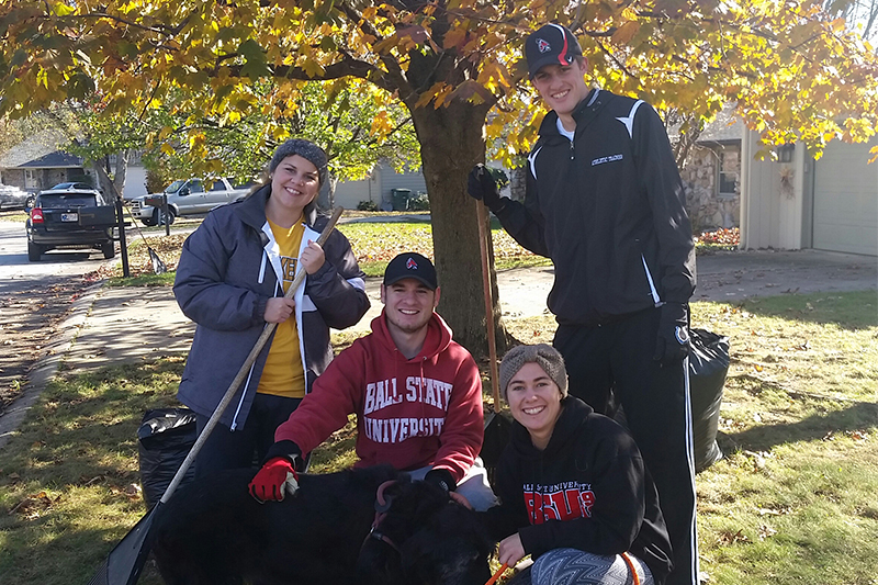 Physical Education Student Association members rake leaves.