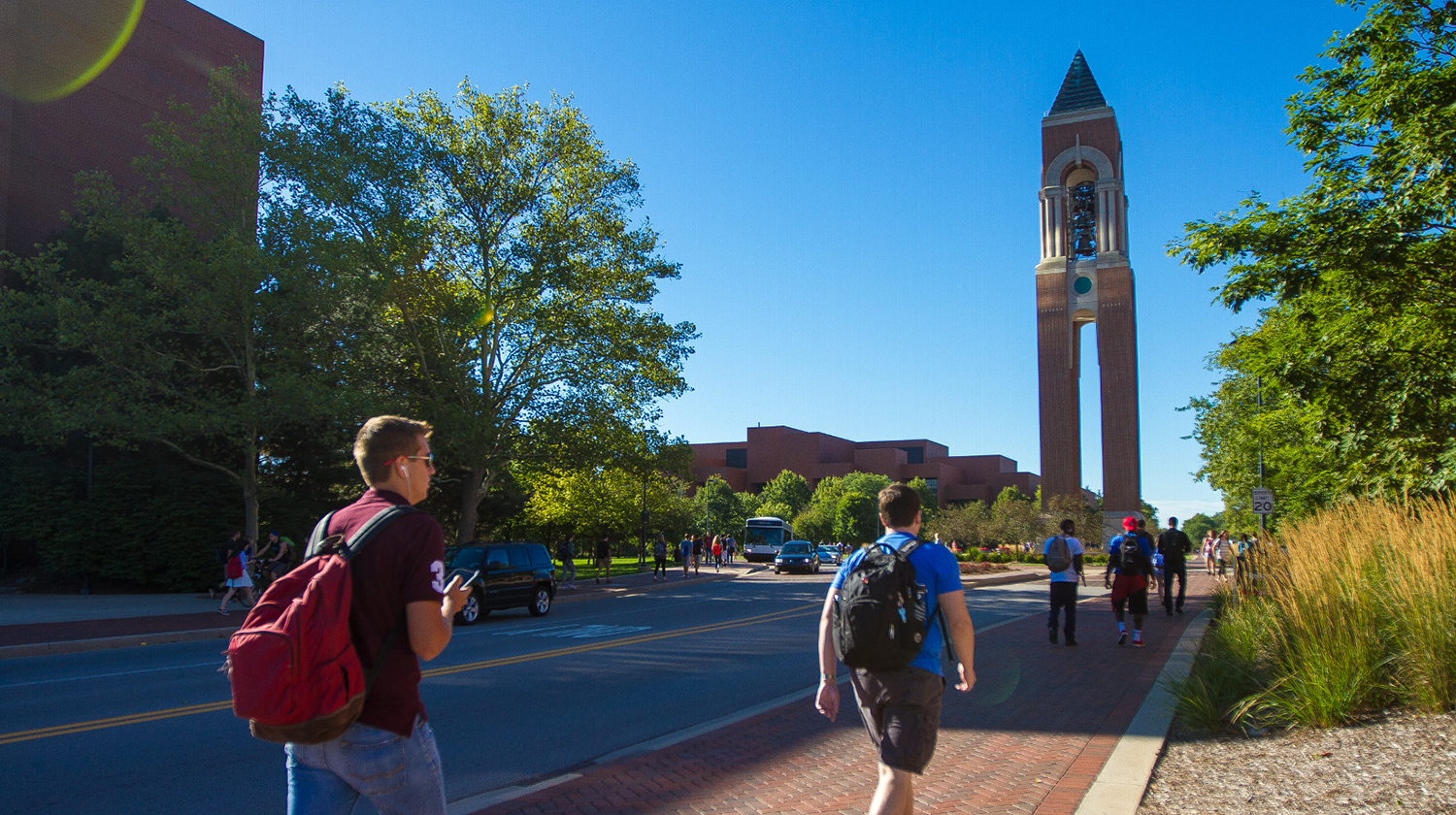 Students walking on campus near the bell tower.