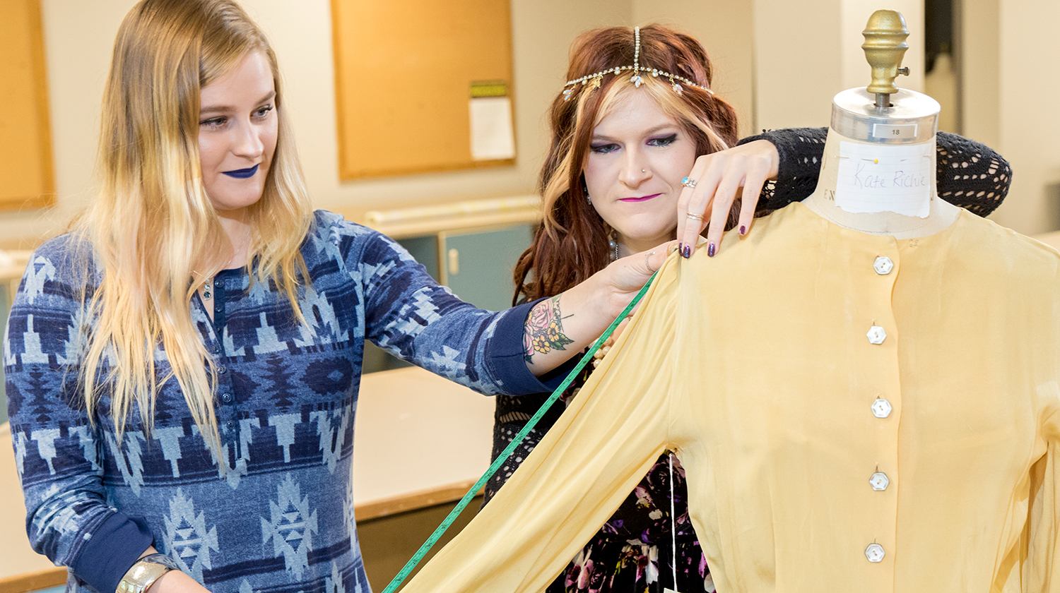 Two apparel design students measure a garment.