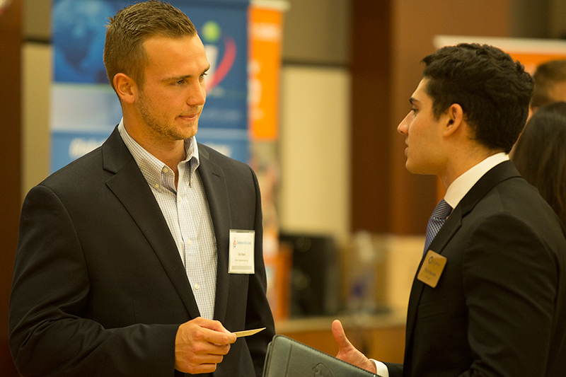 Two sales professionals networking at an event.