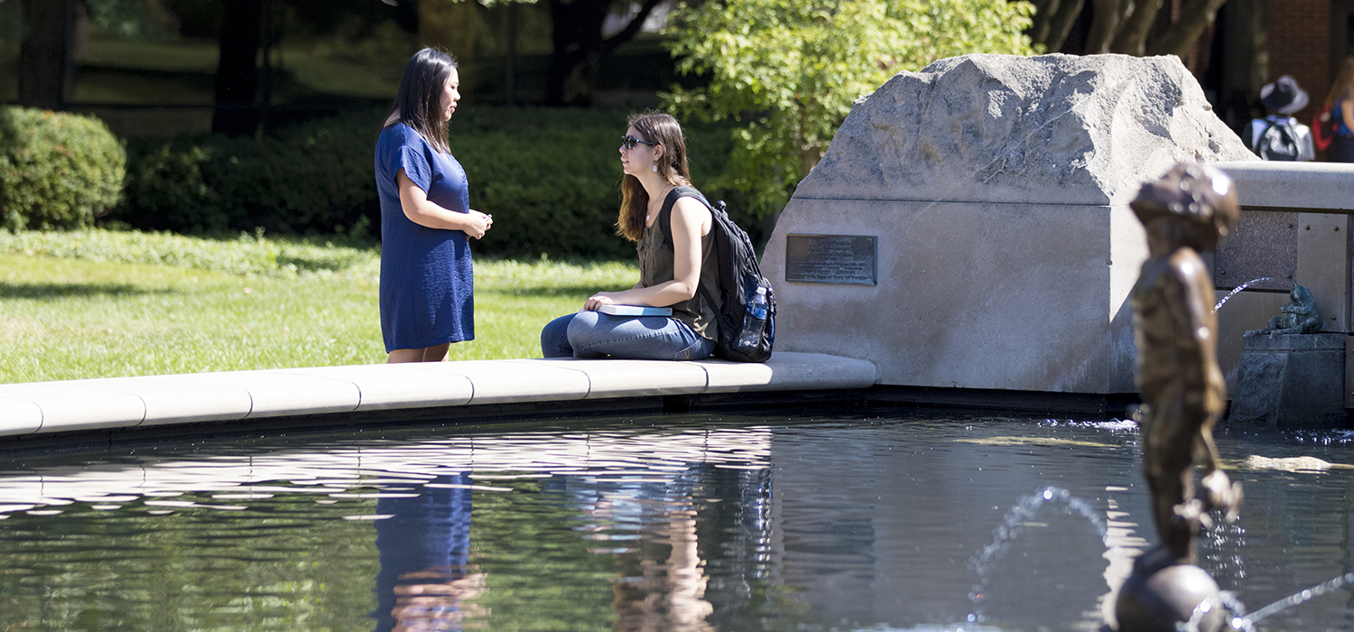 student near 'Frog Baby' fountain