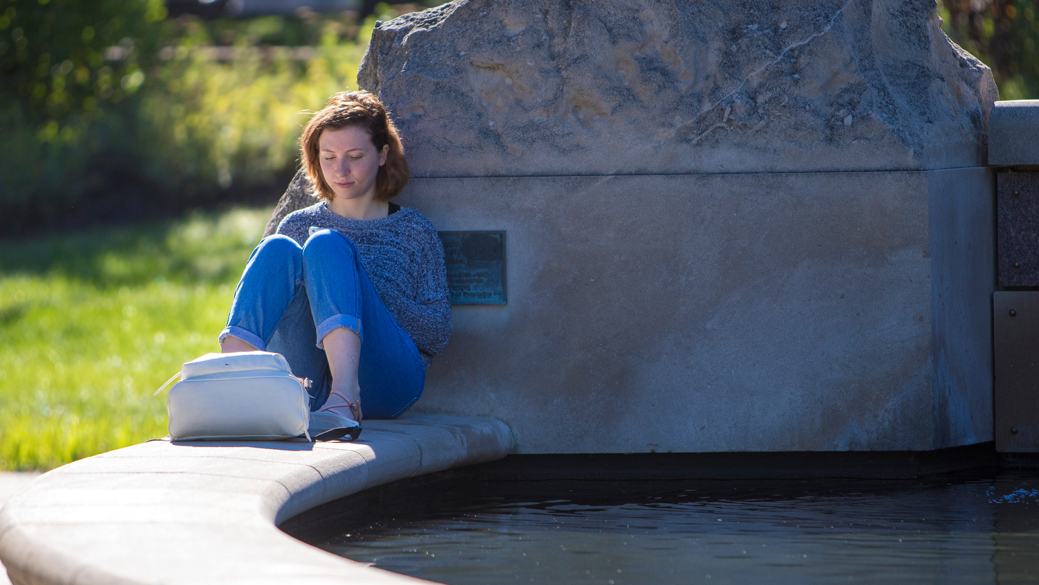 student studying by a fountain