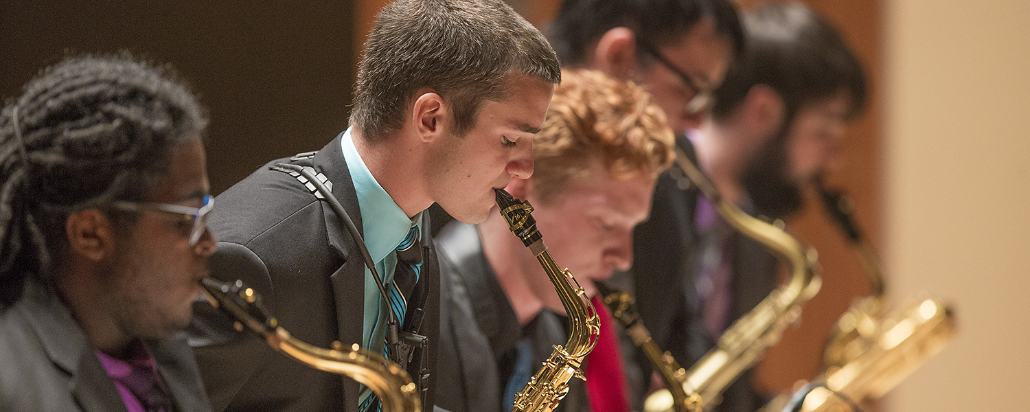 students performing saxophone on stage