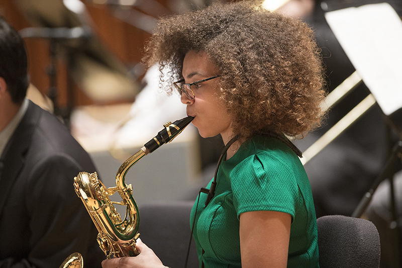 female saxophone player practices on stage