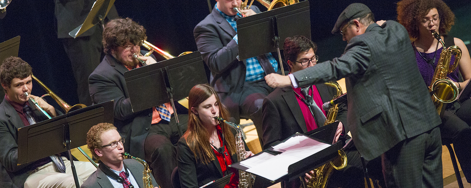 students performing jazz on stage with conductor