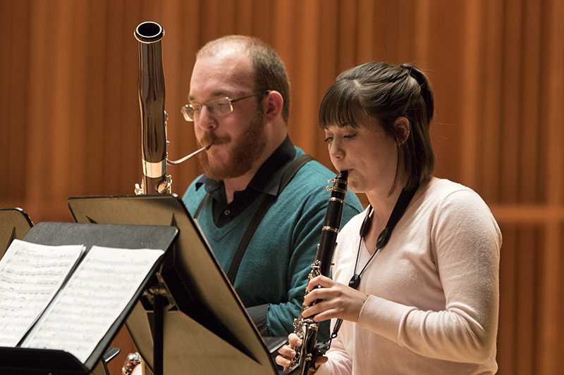 students perform on stage playing the bassoon and oboe
