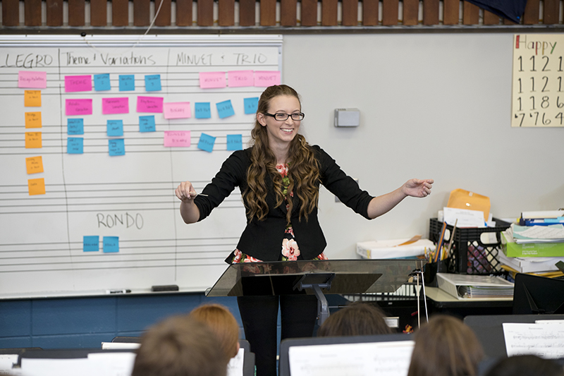 Student practices conducting in front of class
