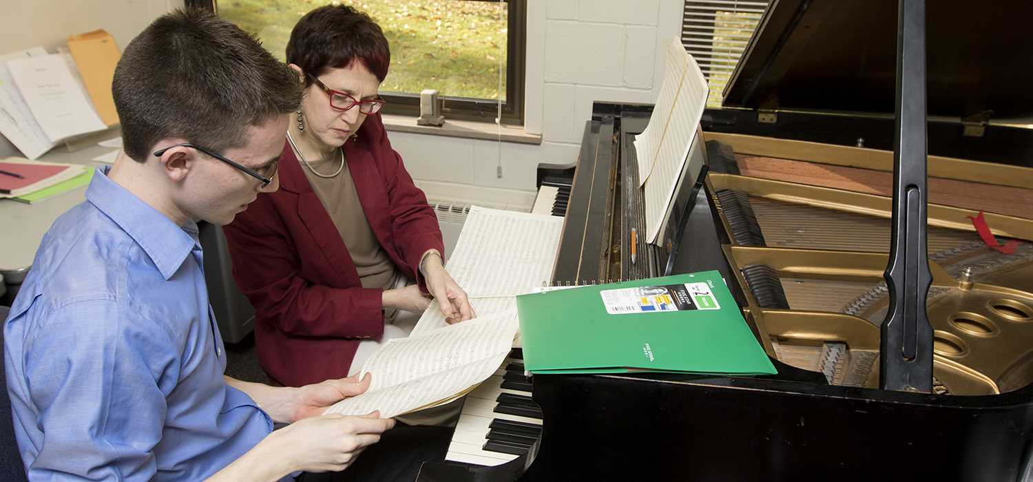 instructor teaches student at piano in a classroom