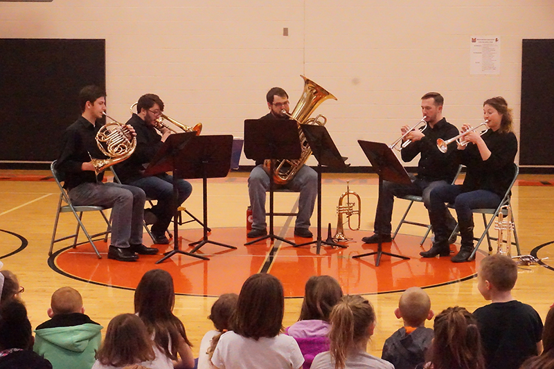 Students performing as a brass quintet on a gymnasium floor