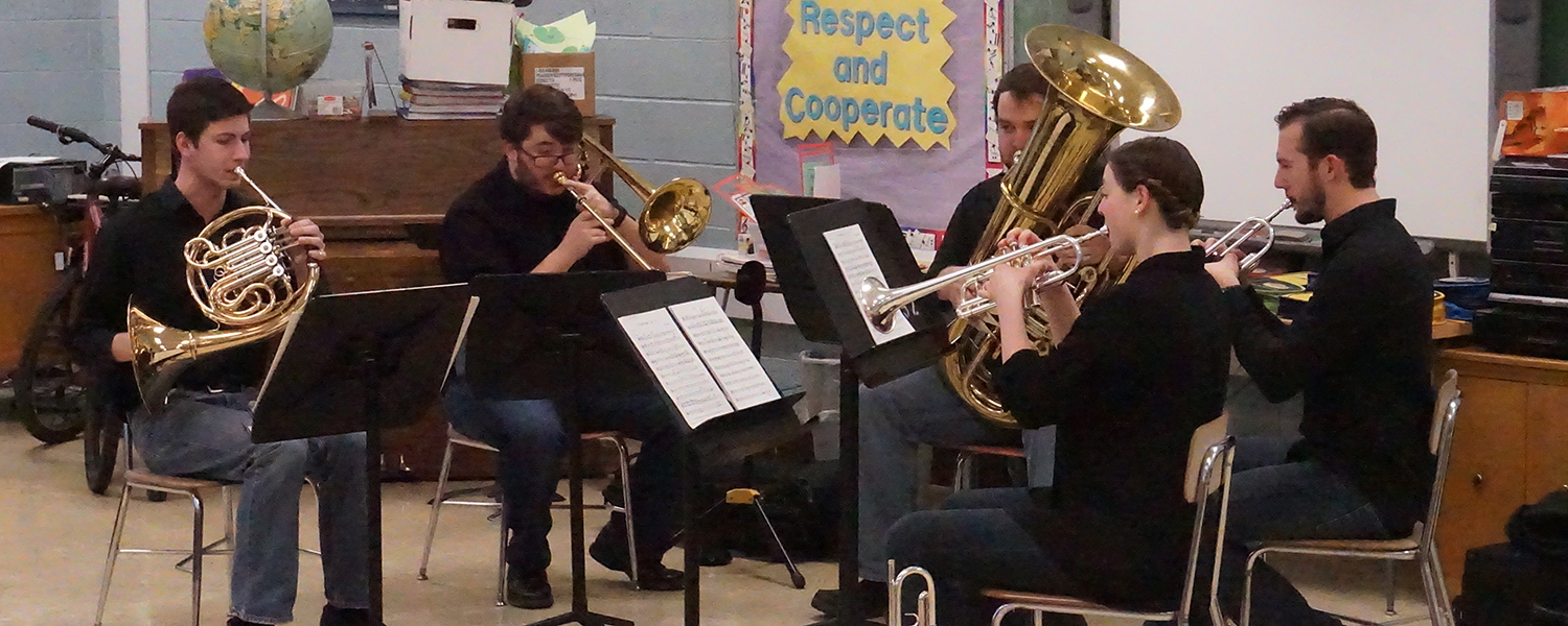 brass quintet performing in a classroom