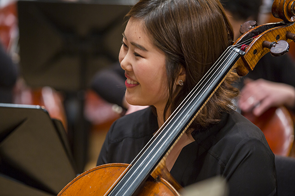 female student playing cello on stage