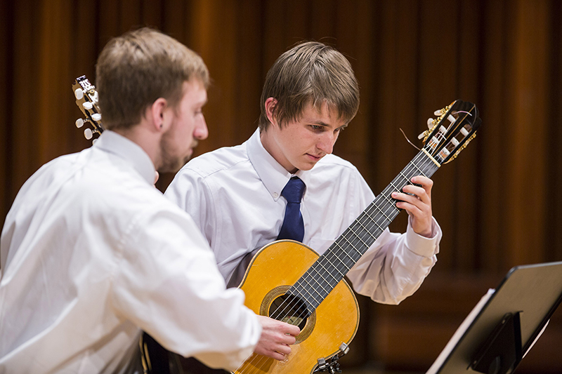 students perform on stage in the guitar ensemble