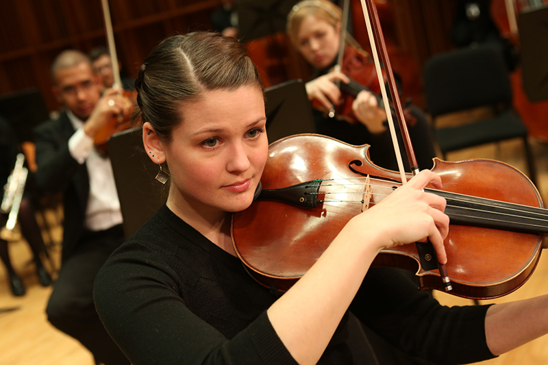 female student plays violin on stage