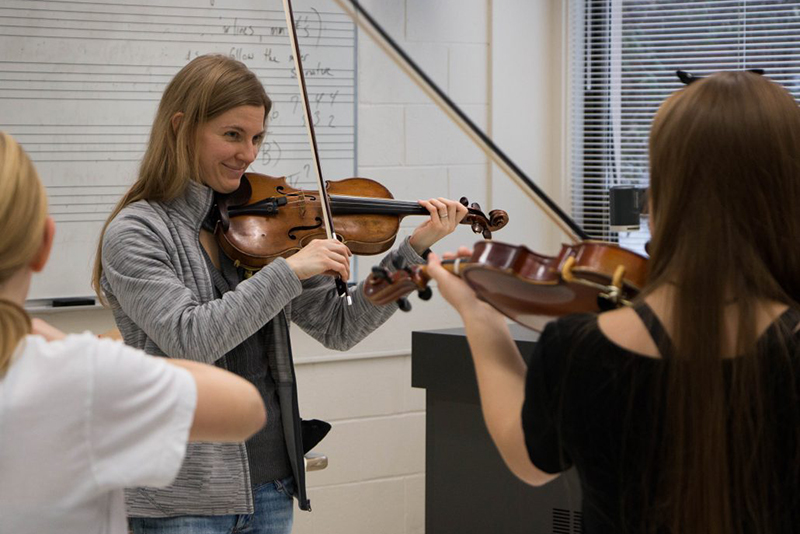 young symphony orchestra practices in a classroom