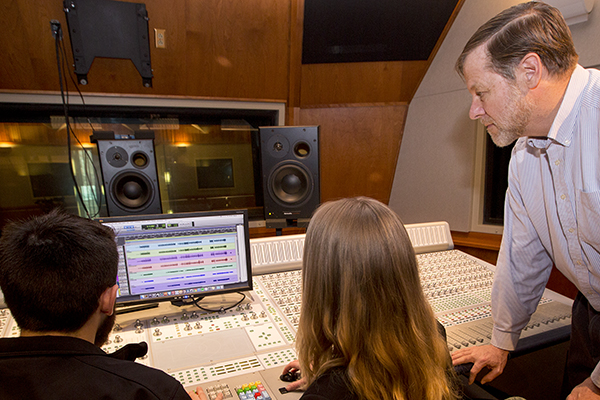instructor and two students working on music media production in a studio